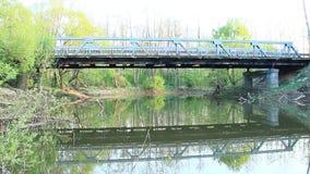 Мост автомобиля через реку отражен в воде в спокойном весеннем дне Пруд в лесе видеоматериал