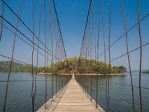 Мост веревочки направляет к сиротливому острову через озеро стоковая фотография
