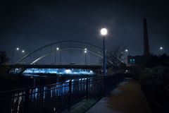 Мост города и городское промышленное здание на ноче Стоковые Фотографии RF