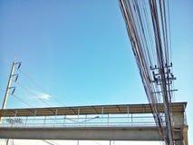 Мост и электрический поляк соединяются к высоковольтным электрическим проводам на предпосылке голубого неба Стоковые Изображения