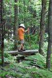 мост мальчика hiking над малым Стоковая Фотография