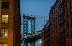 Мост Манхаттана увиденный от Dumbo между кирпичными зданиями на Бруклине на заходе солнца - Нью-Йорке, США стоковое изображение