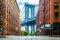 Мост Манхэттена между Манхэттеном и Бруклином над Ист-Ривер увиденным от узкого переулка заключенного 2 кирпичными зданиями на a стоковые изображения rf