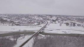 Мост над замороженным рекой в зиме в маленьком городе сток-видео