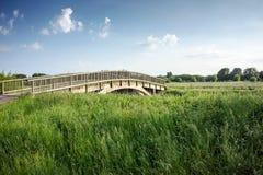 Мост над потоком в сельской местности, белизна голубого неба заволакивает Стоковые Фотографии RF
