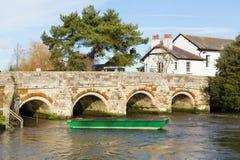Мост над рекой Эвоном Крайстчёрчем Дорсетом Англией Великобританией с зеленой шлюпкой Стоковое фото RF