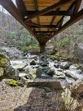 Мост над скалистой водой Стоковая Фотография
