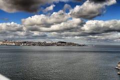 Мост 25-ое апреля в Лиссабоне под облачным небом Стоковое Изображение RF