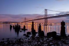 Мост 25-ое апреля и старые руины пристани Стоковые Изображения