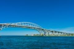 Мост пересекая реку под большое голубое небо стоковые фотографии rf