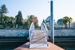 Мост пешехода железный с озером и горы в ярком morni стоковая фотография
