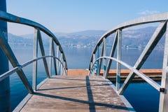 Мост пешехода железный с озером и горы в ярком morni стоковые фотографии rf