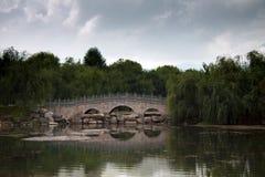 Мост традиционного китайския каменный через озеро потерял в зеленом t Стоковое фото RF