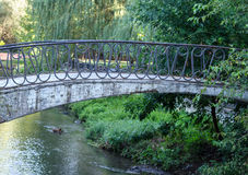 Мост через малое реку в парке Стоковое Изображение