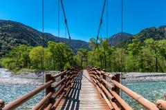 Мост Kamikochi над потоком стоковая фотография