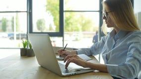 Мотивированная девушка работая на компьтер-книжке и замечать сток-видео