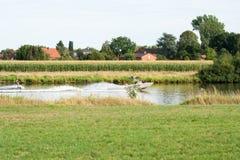 Моторка вытягивает человека на веревочке Wakeboarding на реке стоковая фотография rf