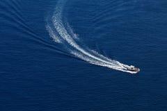 Моторка делает поворот в темно-синем море стоковое изображение