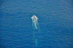 Моторка которая вспахивает через голубое море стоковая фотография
