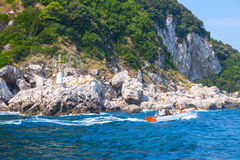 Моторка с туристами идет около прибрежных утесов Стоковое Фото