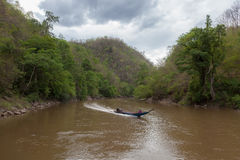 Моторная лодка в пасмурном реке пропуская среди Стоковые Фото