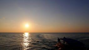 Моторная лодка плавая на море против захода солнца сток-видео