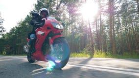 Мотоциклист едет вдоль дороги сток-видео