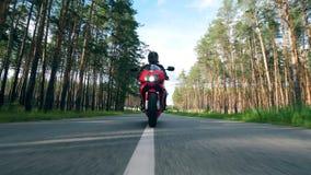 Мотоциклист едет на красном велосипеде на дороге около деревьев сток-видео