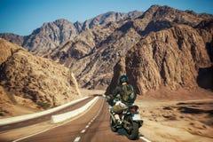 Мотоциклист спешит вдоль живописного шоссе горы пустыни Стоковое Изображение