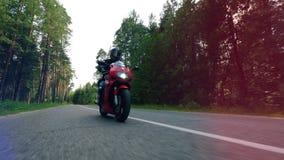 Мотоциклист управляет вдоль дороги леса видеоматериал