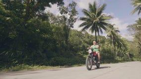 Мотоциклист человека управляя на мотоцикле на дороге с зеленым ландшафтом пальм Зрелый мотоцикл катания человека на дороге внутри видеоматериал