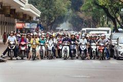 Мотоциклы получили затор движения на дороге с зелеными деревьями в предпосылке на Ханое, Вьетнаме Стоковые Изображения