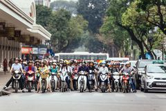 Мотоциклы получили затор движения на дороге с зелеными деревьями в предпосылке на Ханое, Вьетнаме Стоковые Фото