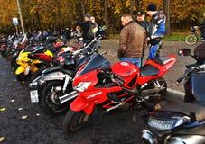 Мотоциклы стоят в ряд Люди смотрят их стоковые фото