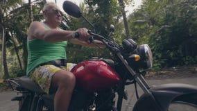 Мотоцикл катания пенсионера на тропической деревне на солнечном дне Пожилое motorbiker человека управляя на мотоцикле на тропичес сток-видео