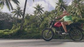 Мотоцикл катания старшего человека на дороге на предпосылке солнечности Зрелый мотоцикл катания человека на зеленом ландшафте пал видеоматериал