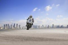 Мотоцикл катания человека большой на шоссе асфальта против городской предпосылки горизонта стоковая фотография rf