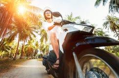 Мотоцикл катания человека под пальмами стоковые фото