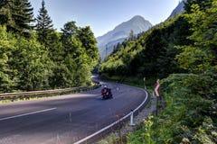 Мотоцикл на изогнутой дороге водя к горам Стоковая Фотография