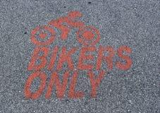 Мотоцикл паркуя только знак, покрашенный в красном цвете на асфальте с силуэтом велосипедиста moto катания стоковое изображение