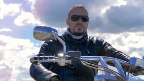Мотоциклисты принимают окружающий взгляд усаживая на его мотоцикл 4K сток-видео