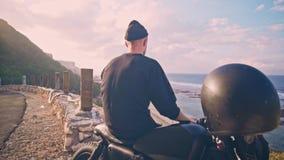 Мотоциклист сидит на его мотоцикле и восхищает красивый вид гор и океана, остановки на пути видеоматериал