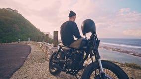 Мотоциклист сидит на его мотоцикле и восхищает красивый вид гор и океана, остановки на пути акции видеоматериалы
