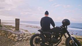 Мотоциклист сидит на его мотоцикле и восхищает красивый вид гор и океана, остановки на пути сток-видео