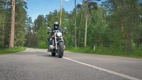 Мотоциклист стороны черепа едет на солнечной дороге видеоматериал