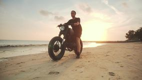 Мотоциклист управляя его мотоцилк на пляже во время захода солнца сток-видео