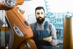 Мотоцикл мужского работника фиксируя неудачный в мастерской Стоковая Фотография