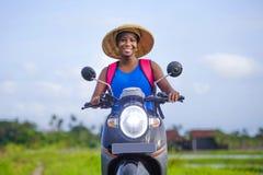 Мотоцилк катания чернокожей женщины молодого привлекательного backpacker туристское афро американское с азиатской традиционной шл стоковое фото rf