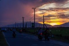 Мотоцилк на дороге вечера с желтым заходом солнца Стоковое фото RF