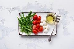 Моццарелла, томаты вишни и arugula, который служат в белых керамических прямоугольных плитах с оливковым маслом над серой предпос стоковое фото